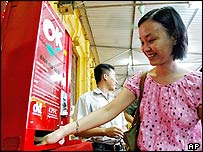 Huynh Hong Ngoc, 29, tries out Vietnam's first condom vending machine at a beer garden restaurant in Hanoi, on Friday, July 9, 2004