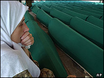 A woman looks at coffins of Srebrenica massacre victims laid out for burial