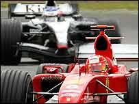 Ferrari's Michael Schumacher pursued by Kimi Raikkonen at Silverstone
