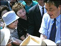 Katsuya Okada, leader of Japan's main opposition Democratic Party, is mobbed by his supporters at a railway station in suburban Tokyo, Thursday, July 8, 2004.
