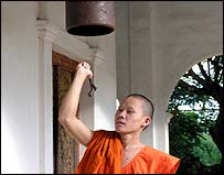 Monk rings bell to announce meditation in pagoda