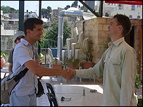 Matthew Price (left) shakes hands with fellow correspondent James Reynolds