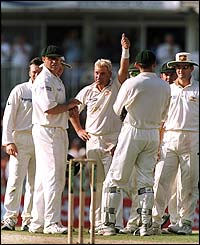 Warne acknowledges the crowd's applause for his 400th wicket