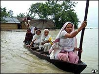 Family leave home by boat in Assam