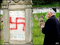 A member of the Jewish community looks at a desecrated tombstone in Herrlisheim, France on 30 April 2004