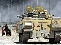 A woman and her child flee Basra as UK troops move in, April 2003