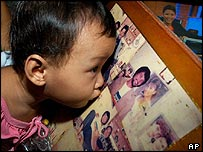 A young relative of hostage Angelo de la Cruz kisses a picture of him