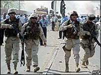 Policías iraquíes y tropas estadounidenses en la escena de la explosión