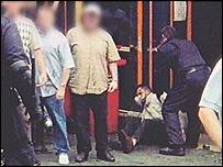 An Asian man lies injured in the Bradford riots
