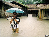 Indian villager carries goat to safety in village of Deuduar