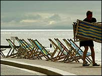 A beach attendant puts out deck chairs at Bournemouth on Thursday