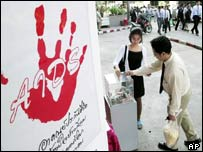 Thai office workers donate money during the international Aids conference