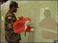 Guard gives clothes to detainee at Camp Delta