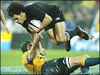 New Zealand's Doug Howlett evades Justin Harrison's challenge