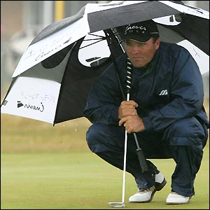 Thomas Levet takes cover from the elements at Troon
