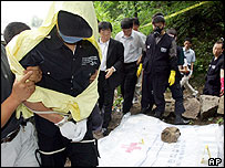 Handcuffed Yoo Young-chul with police as bodies are unearthed