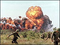 US soldiers in Vietnam run from a napalm attack