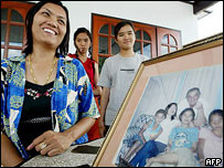 Thai provincial official, Anthika Sarawithee (L) smiles next to a photo of her English partner John