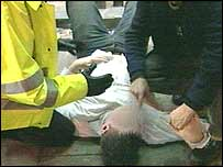 Man on floor being helped by police