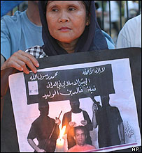 A Filipino Muslim carries a television image of Angelo de la Cruz surrounded by his hooded abductors