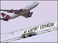 Plane flies near a demonstration banner at Heathrow