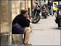 Woman chatting on phone in Paris side-street