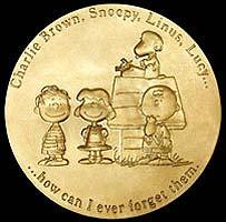 Una cara de la medalla que muestra a Charlie Brown, Snoopy, Linus y Lucy.
