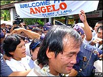 Crowd greets released Filipino hostage Angelo de la Cruz, escorted by police, upon arriving in his hometown of Buenavista (23/07/2004)