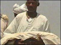 Men bury the body of a baby refugee from Sudan