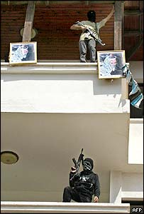 Masked Palestinian militants of the al-Aqsa Martyrs Brigades occupy the balconies of the Khan Yunis governorate building