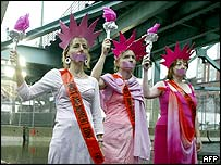 From left: Protesters Gael Murphy, Medea Benjamin and Robyn Miller dressed as gagged Statues of Liberty