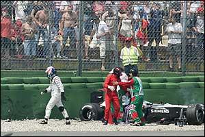 McLaren driver Kimi Raikkonen walks away after crashing into the tyre barriers
