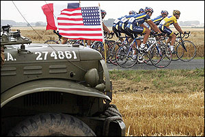 US Postal riders move past an American arrmy jeep