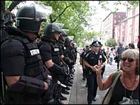A woman flashes the peace sign to police in riot gear