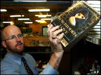A man removes a copy of 'Forbidden Love' from a bookshelf