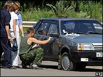 Investigator examines car damaged in 26 July blast