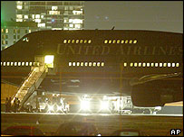 Police officers wait at the bottom of the stairs leading to the United Airlines plane at the southern end of the Sydney international airport, Tuesday, July 27, 2004