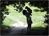 Mother and child playing in a wooded field