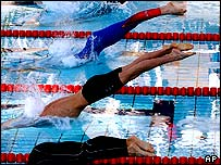 Swimmers dive in at the Olympic pool in Athens during a test event