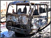 The charred remains of a bus sits at the site of a suicide car bombing in Baquba