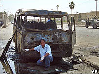 Iraqi crouches in front of charred minibus
