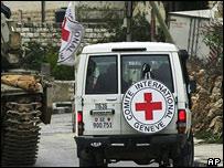 Red Cross lorry drives alongside a tank