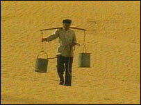 Man carrying pales through the desert