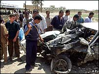 Iraqis look at the wreck of a car after a bomb attack in Baquba on Wednesday