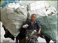 A man eats as he hauls a load of polystyrene on his tricycle in Beijing, July, 2004