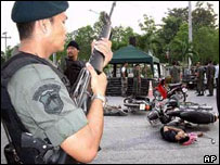 A Thai policeman stands guard over the body of a dead soldier