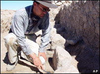 An anthropologist examines the remain of an pre-Inca brewery, Peru