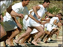 Barefoot runners wearing tunics take part in a footrace in the ancient stadium of Nemea
