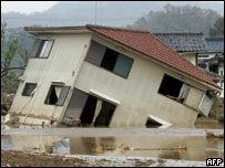 A woman washes her hands next to a collapsed house destroyed by typhoon Tokage in Izushi town, Hyogo Prefect