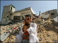 A father and son sit near the remains of their home in the Jabaliya refugee camp, northern Gaza Strip